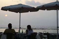 Las Palmas, end of a beautiful day (christing-O-) Tags: sunset vacation woman man beach beer umbrella couple august parasol 2010 laspalmas islascanarias canaryisland lascanteras guardasol lescanaries