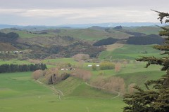 View across farmland, snow capped ranges in the distance