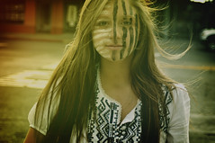 Paint. (JesseMari) Tags: street portrait brown color girl face lines shirt hair person paint wind stripes facepaint nikond90