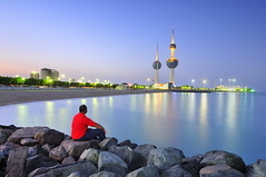 Looking at the towers (Talal Al-Duolye) Tags: blue red sea motion beach colors modern landscape person lights nikon rocks sad towers tokina hour thinking kuwait talal q8 d300 kuwaittowers alduolye