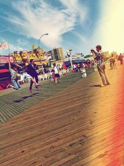 Boardwalk @ Coney Island (kukasphotos) Tags: new york city nyc blue light summer people urban usa white ny black colour reflection building green art apple water clouds lens liberty island jump colorful exposure shot nathan awesome experiment sunny retro level boardwalk 1970 colourful coney leak 2010