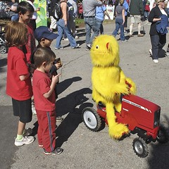 IT WAS A ONE-EYED, LONG-HAIRED, BIG-MOUTHED, YELLOW-COLORED, HEIGHT-CHALLENGED TRACTOR OPERATOR. (NC Cigany) Tags: street red sky people cute water yellow museum kids square funny waterfront joke statefair wwii gray navy fair raleigh battleship tease oneeye capefearriver 6548 staterfair