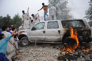 "Afghanistan youth destroy United States embassy vehicles after civilians were killed by the SUVs. Demonstrators chanted ""Death to America"" and prompted the dispatch of military occupation forces to put down the unrest. by Pan-African News Wire File Photos"