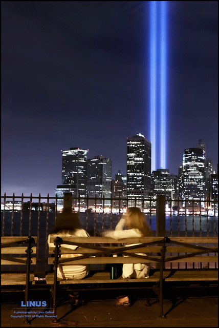 This year's Tribute in Light 9/11 memorial, taken from the Brooklyn Heights Promenade. Two women watch and talk in the foreground.