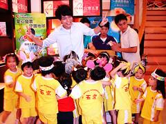被小朋友簇擁的環保大使林宇中,不忘呼籲大家捐發票,保護山林海洋與溼地。