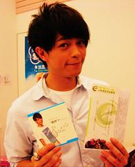 擔任一日環保店長的林宇中,拿著台灣環境資訊協會簡介和環保單曲CD ,和現場民眾分享環保的重要。