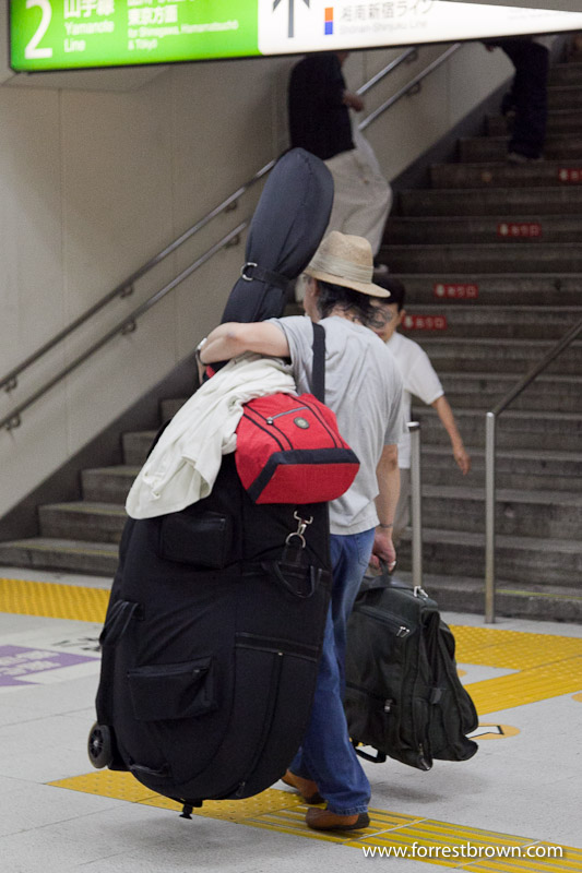 Carrying large musical instruments on the trains in Tokyo.  Musical Instrument, Train, Train Station, Tokyo, Japan.