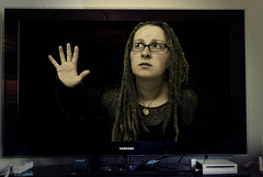 Day 107 .let me out. (Michelle Elaine.) Tags: portrait selfportrait art girl oneaday television dreadlocks photoshop self dark one tv trapped whimsy media alone technology stuck autoportrait fear fame dream samsung naturallight screen sp remote nightmare 365 scared 1740mm watermark actions selfie wii killyourtv project365 365days canon40d