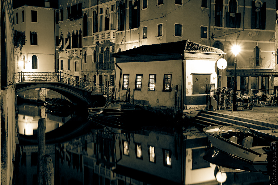 Small house with a boat on a canal at night, Venice, Italy