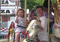 Speck and Mom grinning on a classic carousel