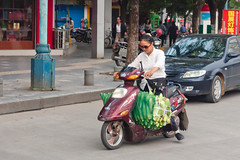 Woman on a scooter with a lot of corn in Guilin