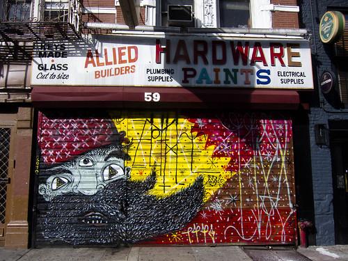 Painted steel rolldown gate of East Village hardware store