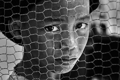 Andong Village, Cambodia - Remove the fence and you'll know me better (Mio Cade) Tags: boy portrait eye fence kid cambodia village child phnom scavenger penh andong