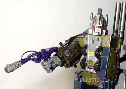 G1 Bruticus holding Shockwave