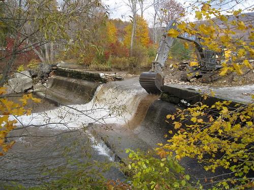 An excavator begins demolition of Briggsville Dam.