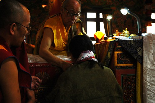 On the throne, His Holiness Jigdal Dagchen Sakya gives blessed katag (kata) and protection cord to his daughter in law, Dagmo Lhanze Youdhen Sakya, with a master of ceremonies, Lamdre, Tharlam Monastery of Tibetan Buddhism, Boudha, Kathmandu, Nepal
