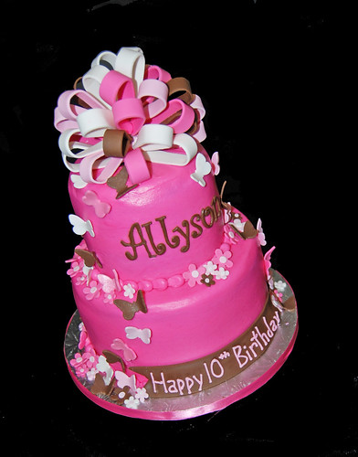 bright pink, brown and white 2 tier birthday cake with butterflies topped with a large bow
