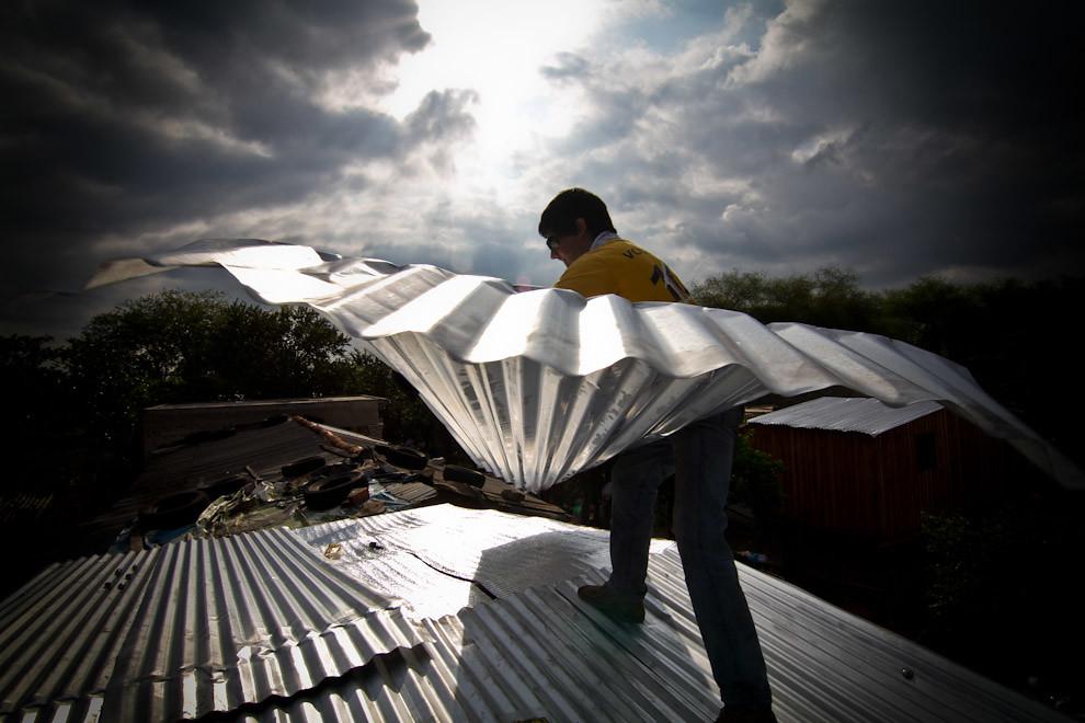 Un voluntario coloca las últimas chapas de zinc sobre el techo de la vivienda en horas de la tarde del sábado. (Tetsu Espósito - Lambaré, Paraguay)