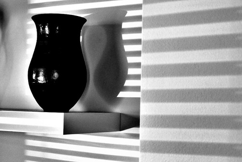 Vase on shelf in alcove with pronounced lines of shadow from hard light through venetian blinds