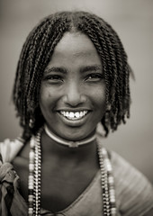 Miss Beride, Karrayyu girl, smiling, Ethiopia (Eric Lafforgue) Tags: africa people blackandwhite haircut girl smile face childhood smiling vertical horizontal youth collier outside outdoors person necklace kid child noiretblanc portait joy tribal headshot jeunesse innocence ethiopia tribe hairstyle enfant fille sourire bonheur naivete personne humanbeing joie tete visage hapiness contemplation coiffure afrique headandshoulders tribu dehors eastafrica enfance abyssinia ethiopie sourir exterieur lookingatcamera traditionalclothes blackandwhitepicture 5546 abyssinie vueexterieure afriquedelest traditionalhairstyle etrehumain photoennoiretblanc regardantlobjectif kereyu karayu peoplesoftheomovalley teteetepaules karrayyu peuplesdelavalleedelomo coiffuretraditionelle tribudeskarrayyus karrayyutribe peuplekarrayyu karrayyupeople habittraditionnels