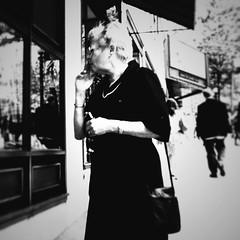 Puff n Pearls (Star Rush) Tags: cameraphone seattle street city portrait urban blackandwhite bw woman dress candid watch pearls smoking sidewalk mobilephone iphone photofx filmlab iphoneography