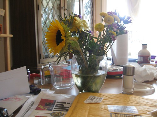messy dining room table with flowers