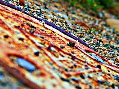fruity pebbles (tarmarlou) Tags: abstract color macro metal closeup yard circle triangle rust rocks stones ground pebbles warehouse cap cover junkyard tilt rubble fruitypebbles colorsbstract