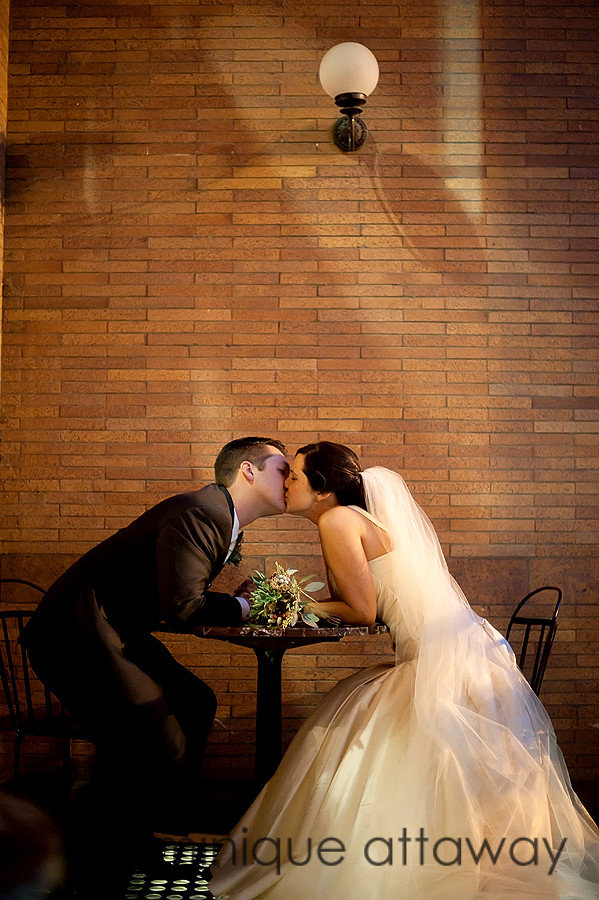 newly weds sitting at a cafe table kissing