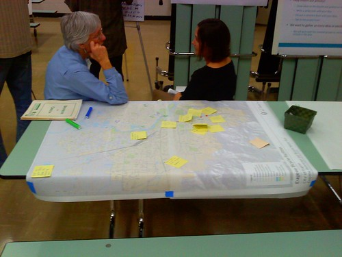 Participants discuss options near a map full of suggestions