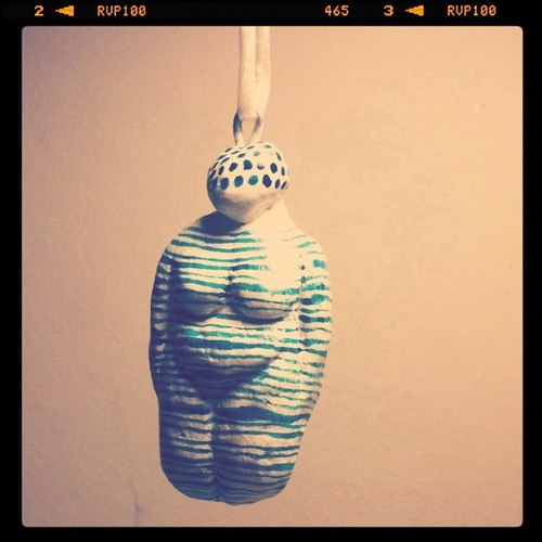 Photo of a fat figurine with no hands or feet, sort of like the Venus de Willendorf, painted white with green horizontal stripes and polka dot hair.