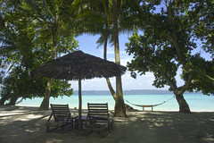 Chairs on shady beach (FullofTravel) Tags: ocean travel blue sea sky india tree green beach clouds relax landscape boat sand chair holidays deckchair wind coconut indianocean lagoon palm shade thatch breeze emerald tropics nicobar torquise