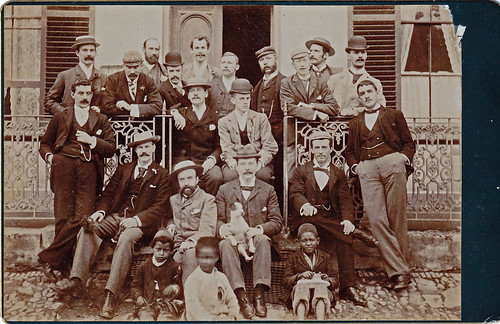 Group of men with dog and African boys. British East Africa? North Africa?