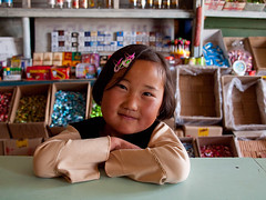 Little shop keeper (Evgeni Zotov) Tags: people girl smile cake shop asia village child counter candy sweet cigarette goods keep merchandise kyrgyz sell kyrgyzstan seller bonbon hairpin assistant commodity keeper wares kirghizistan kirgistan kirgizia alay kirgizistan sarytash kirgizi kirgisistan  kirguistan kirghizia krgzistan quirguisto
