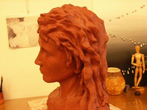 Sculpture en terre figurative vue de profil représentant la tête légèrement inclinée d'un jeune homme aux cheveux longs et ondulés avec une expression à la fois rêveuse et triste – Sandrine Vallée