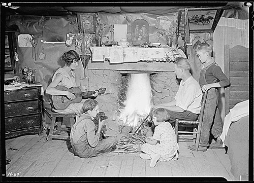 """The Glandon family around the fireplace in their home at Bridges Chapel near Loydston[sic], Tennessee. Glandon's wife plays both the guitar and the organ."", 10/31/1933"