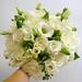 white roses, lisianthus, freesia, green hypericum berry