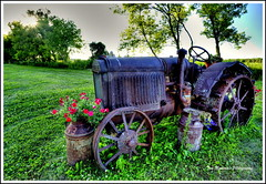 Iron-wheeled Wonder (Tom Mortenson) Tags: tractor antique rusty digital canon summer farm farmtractor canoneos canon6d outdoor farmfield wisconsin usa america northamerica midwest centralwisconsin marathoncounty marathoncountywisconsin mccormick mccormicktractor antiquetractor rural country hdr tonemapping photomatix geotagged milkcans petunias pastoral scenery scenic farmimplement ironwheels 1740l