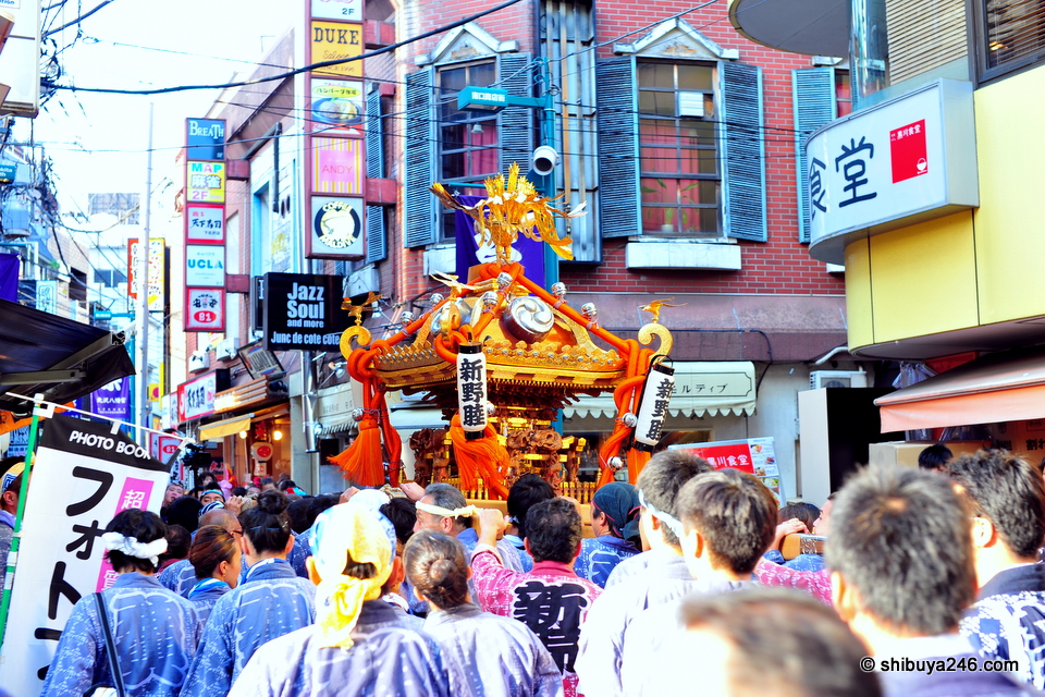 The omikoshi gets carried through the narrow streets