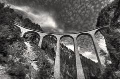 landwasser viaduct with fleecy clouds (Toni_V) Tags: bridge bw monochrome schweiz switzerland blackwhite suisse unesco viaduct worldheritage 2010 weltkulturerbe d300 sigma1020mm rhätischebahn photomatix greatphotographers landwasserviadukt filisur hdrsingleraw capturenx dsc3006 100829 ©toniv