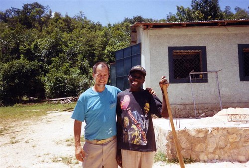 Image of Jeff Behringer with a Haitian adult, a member of a Haitian community helped by Jeff's expertise in stone masonry and by profits from Behringer Stone Masonry company