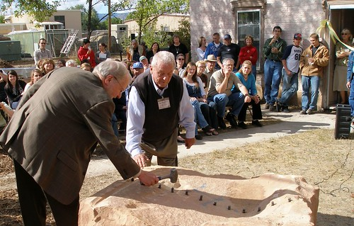 Dave Conine, Utah Rural Development State Director, (left) followed directions in cutting 4,000 pound stone in half the old fashioned way, without any power tools.