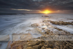 A new dawn. (Stuart Stevenson) Tags: longexposure sky shells seascape motion seaweed water clouds sunrise scotland sand rocks fife tide earlymorning dramatic windy stormy erosion redrocks sunburst eastcoast sunflare kingsbarns eastneuk limpits milkysea