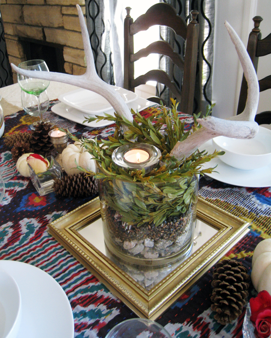 antlers centerpiece on a vintage mirror with pinecones & white pumpkins silver and white dishes on ikat