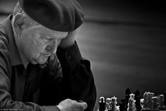 Grandmaster. (Neil. Moralee) Tags: neilmoralee usa2017neilmoralee chess grandmaster master grand player man portrait close face people playing concebtration beret pieces check mate king queen bishop pawn board black white bw blackandwhite mono monochrome good evil battle fight bandw mature old competition champion fide neil moralee nikon d7200 candid street new orleans usa louisiana hat lean tournament