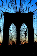 Bridge Tower Silhouette (wyojones) Tags: n new newyork newyorkcity manhattan eastriver lights bridge walkway pedestrian cyclists people brooklynbridge nationalhistoriclandmark nationalhistoriccivilengineeringlandmark sunset dusk tower flag rwilight lamps cables silhouettes wyojones np