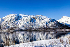 Tiny man vast nature (Jaap Coorens) Tags: small blue ship reflectie winter reflection red alone lofoten white beauty mountain fjord sloop snow