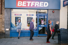 Betfred (Howie Mudge LRPS BPE1*) Tags: canon canonet ql17 giii canoncanonetql17giii fujicolor fujicolorc200 35mm film photography photographer negative scan analog analogphotography candid casual people men women betting shop betfred walk walking lean leaning windows door wall sign aberystwyth ceredigion wales cymru uk travel travelling traveller color colour