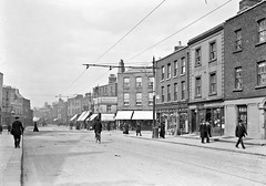 """""""Harcourt Street, Dublin"""" is actually Charlotte Streest at Harcourt Road (National Library of Ireland on The Commons) Tags: eason easonson easoncollection easonphotographiccollection glassnegative 20thcentury nationallibraryofireland jwhalloran gallaghers streetscene dublin leinster dublin2 tramtracks bowlerhat bicycle rgkirkham woodmilnerubberheels thebootrepairinghouse charlottestreet charlemontstreet probablecataloguecorrection cataloguecorrection harcourtroad nolongerstanding"""