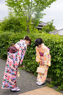 Young women in kimono bowing each other on street