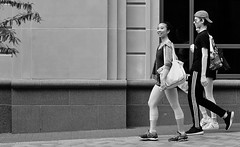 Tiny Dancer (burnt dirt) Tags: houston texas downtown city town mainstreet street sidewalk corner crosswalk streetphotography fujifilm xt1 bw blackandwhite monochrome purse bag cellphone phone girl woman people person asian dancer ballet ballerina walking smile laugh crowd group three tights leggings yogapants bun